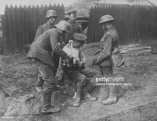 German orderlies dressing the wounds of an injured British soldier