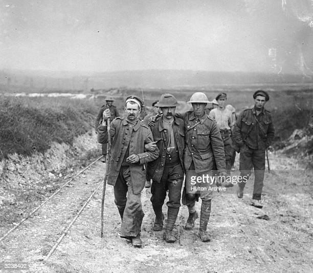 Two wounded British soldiers walk arm-in-arm with a wounded German prisoner as they walk on a dirt road towards a dressing station, World War I. The...