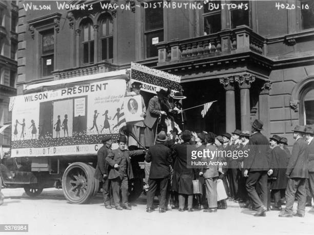 Women distributing buttons from the Wilson Women's Wagon on which they are campaigning for the reelection of Woodrow Wilson as President of the...