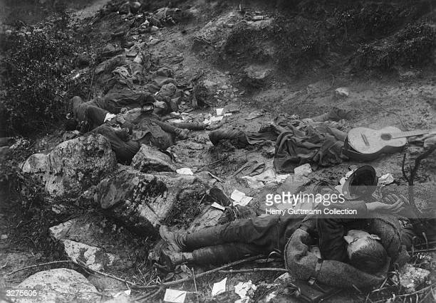 A group of dead Italian soldiers killed during the course of a sudden Austrian attack in the mountains near Cividale Belongings including a guitar...