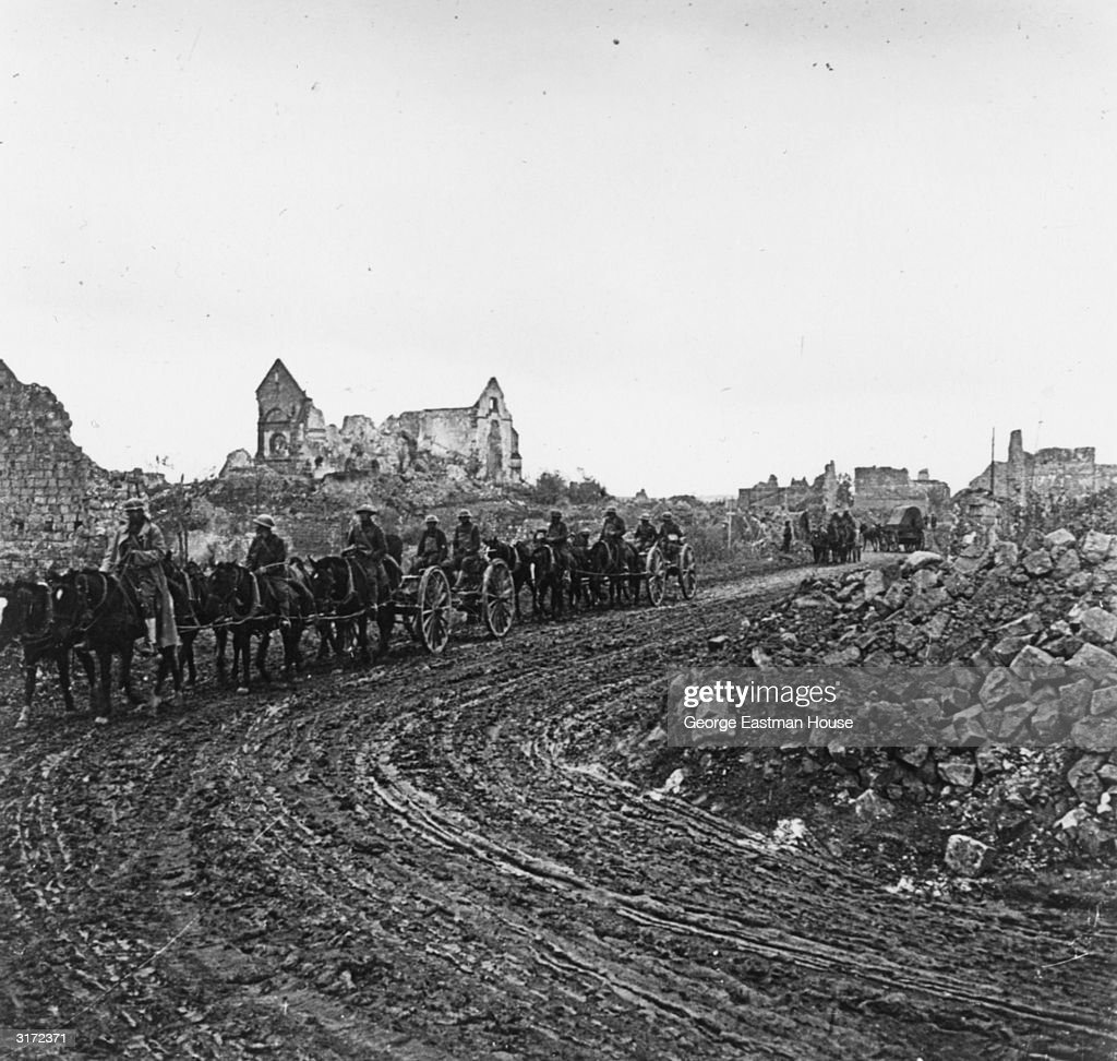 An American convoy of horse-drawn carriages travels on a muddy road past bombed buildings and rubble, as it leaves the Somme, France, during World War I.