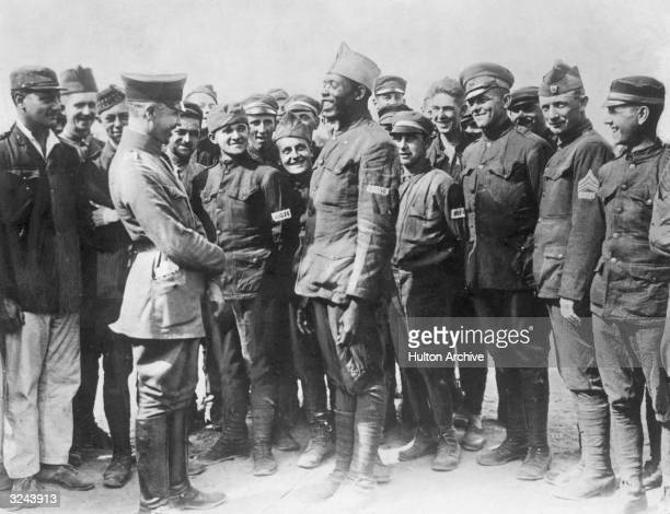 German officer interrogates a smiling AfricanAmerican soldier from a Harlem regiment as other Allied prisoners of war laugh in the background Western...