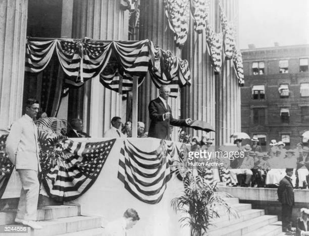 US president Woodrow Wilson making fists with his hands while speaking from a booth in front of a building's large columns Both the speaking booth...