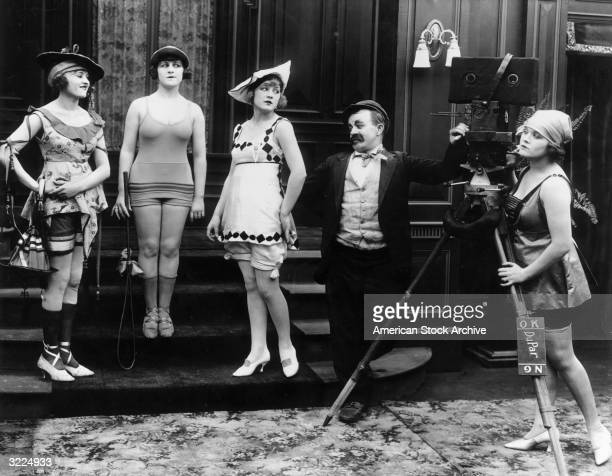 American actor Chester Conklin looks on while Mack Sennett's Bathing Beauties pose on a staircase during the filming of one of the director's silent...