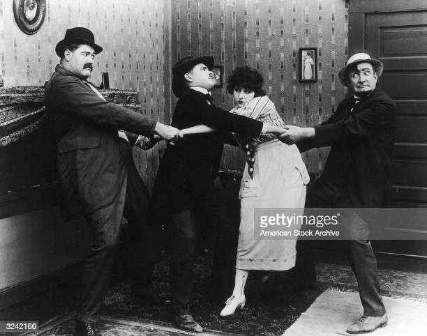 American actors Wayland 'Tiny' Trask and Charles Murray pull a young man and woman in either direction in a still from a Keystone comedy film