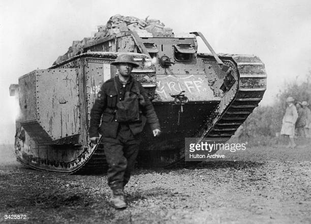 An American soldier walks ahead of an MKIV British-made tank.
