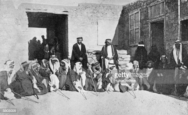 British soldier author and adventurer Thomas Edward Lawrence and the Emir Faisal king of the Helaz later Faisal I King of Iraq confer with Bedouin...