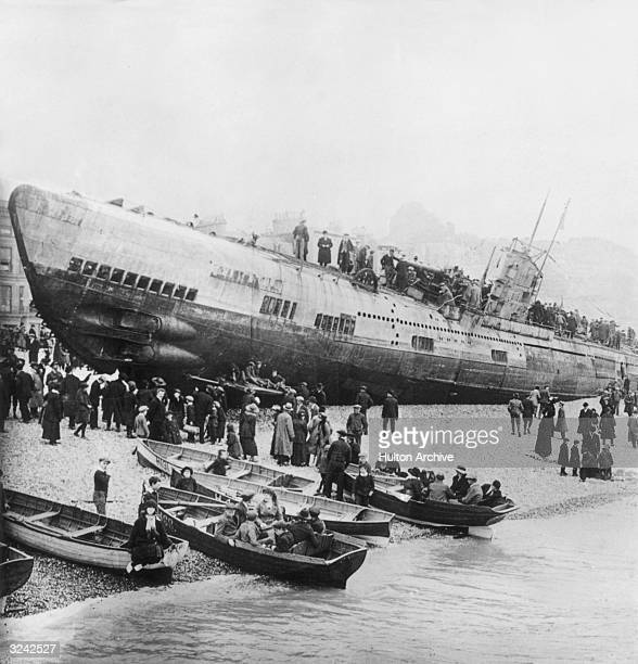 Citizens of a south England coastal town walk on and around a German U-boat left stranded on shore after the end of World War I. Large groups of...