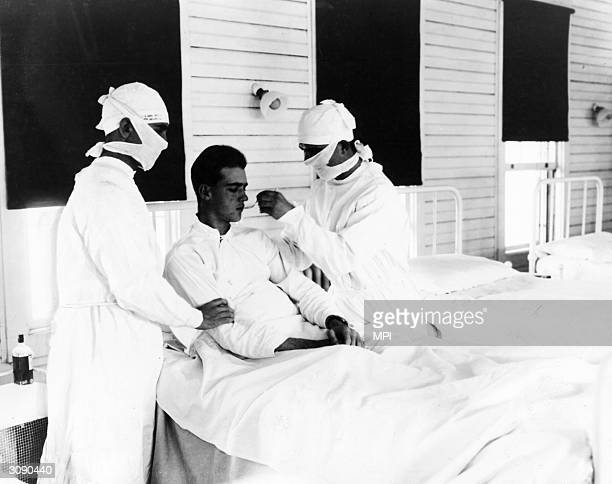 Doctors giving treatment to an influenza patient at the US Naval Hospital in New Orleans