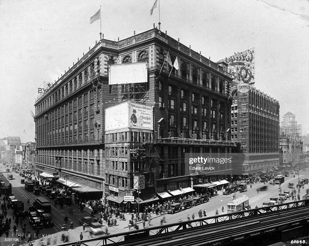 Exterior view of Macy's department store on 34th Street and Sixth Avenue, New York City. There are trolley cars and pedestrians in the intersection and elevated train tracks in the foreground.