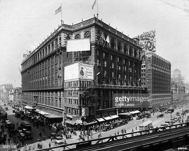 Exterior view of Macy's department store on 34th Street and Sixth Avenue New York City There are trolley cars and pedestrians in the intersection and...