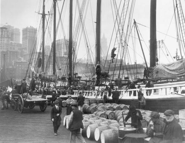 Workers unload crates and barrels on the Fulton Street...