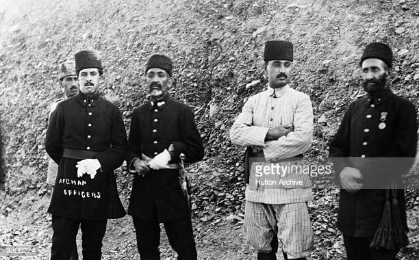 Afghan officers stand in a line in front of a rocky hill during the Third Anglo-Afghan War.