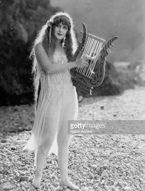 An actress plays a lyre strung with pearls in the fantasy sequence from the film 'Folly of Vanity'