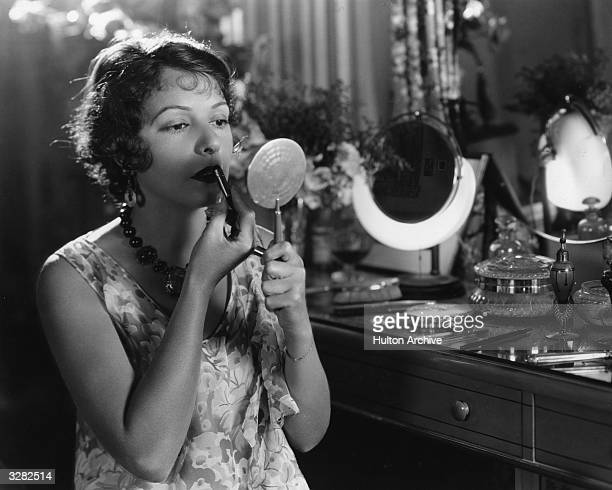 Norma Talmadge the American silent screen heroine who was contracted to United Artists applying lipstick with particular care at her dressing table...