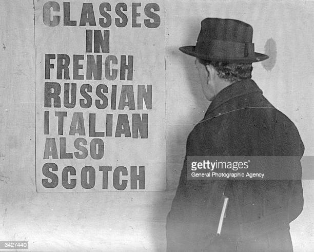 A man reading a sign at a London Language School advertising classes in French Russian Italian and even Scotch