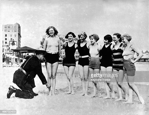 CITY NJ circa 1920 A police officer is measuring the swimming suits of young women on the beach circa 1920 in Atlantic City New Jersey