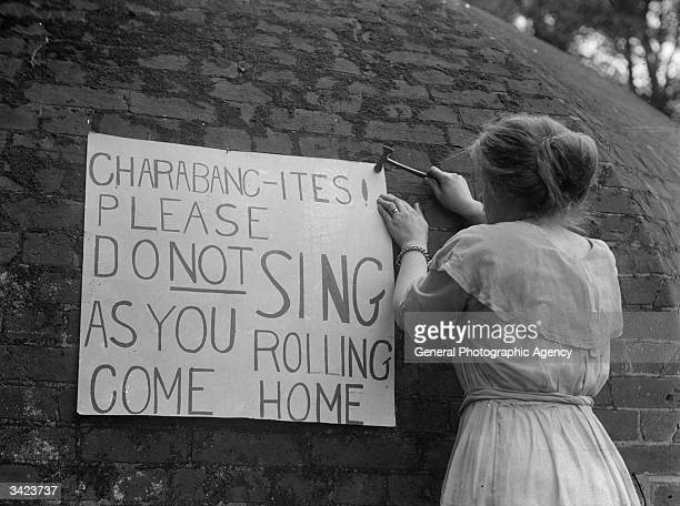 A woman erects a sign to a wall asking the occupants of charabancs an early form of motor coach not to disturb residents with their singing