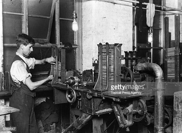 A worker places cedar slats into a machine which will place grooves into them for making pencils