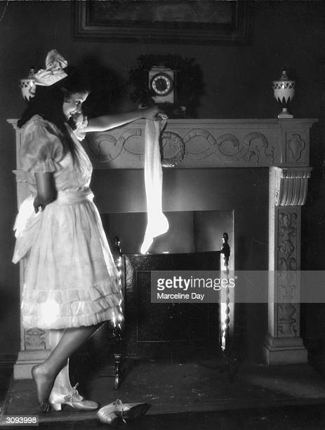 A young girl hangs one of her stockings by the fire to await the arrival of Father Christmas