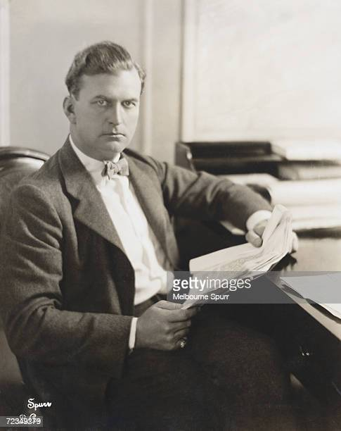 American film director and producer Thomas H. Ince reads through a script at his Culver City studio, California. He died under mysterious...