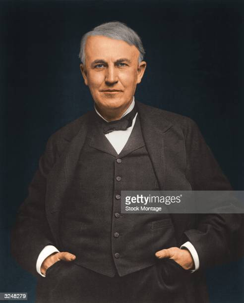 American inventor Thomas Alva Edison wearing a black suit with his hands in his pockets