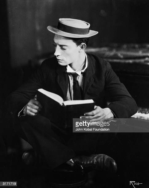American silent screen comedian and actor Buster Keaton curled up with a book