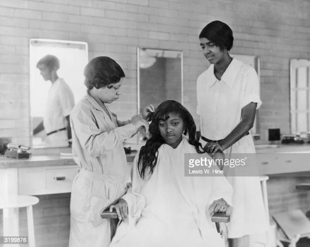 An African-American woman sits in a chair, wearing a smock, while one woman curls her hair and another woman watches in a beauty salon. Photo...