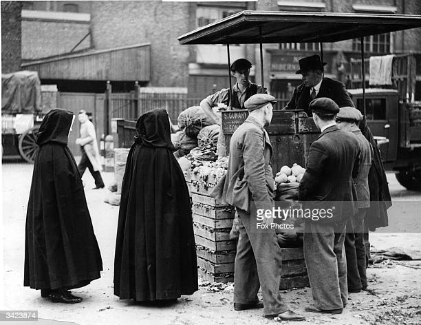 Cloaked nuns queuing for vegetables at Borough Market near London Bridge south east London