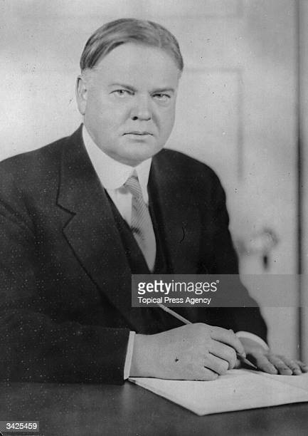Herbert Hoover , later the 31st President of the United States, seated at a desk writing.