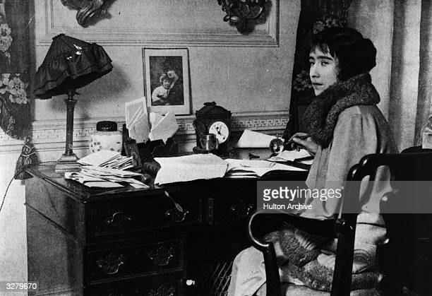 Lady Elizabeth BowesLyon future Queen Consort to King George VI sitting at a desk