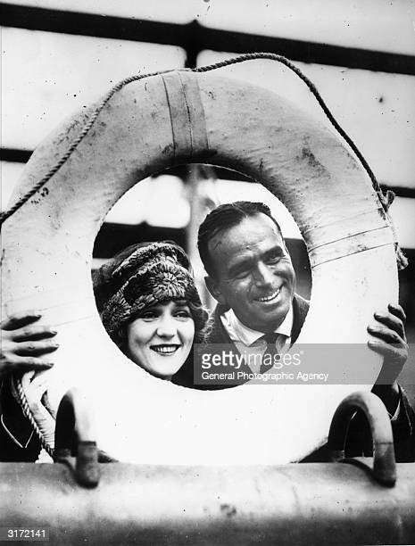 Married actors Douglas Fairbanks and Mary Pickford framed in a life ring just before setting off on their belated European honeymoon on board the...