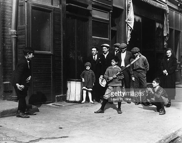 One boy pitches a ball to another boy holding a bat as some adults and a child stand behind the batter on a city sidewalk