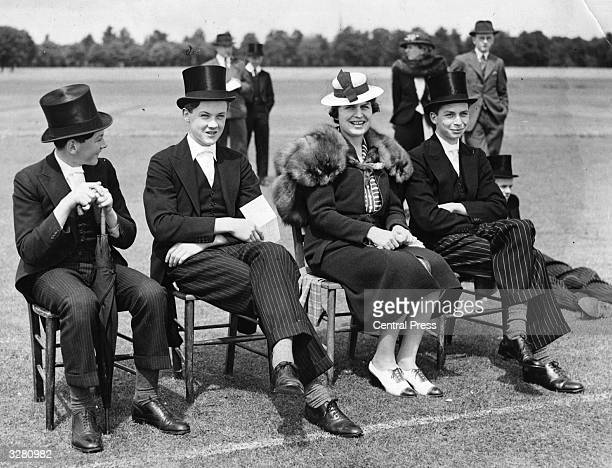 Pupils at Eton sit at the sidelines and watch a cricket match.