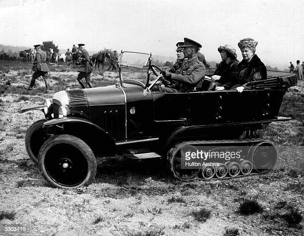 Queen Mary with Princess Mary, the Princess Royal being driven across rough ground in a tracked car by Army officers.