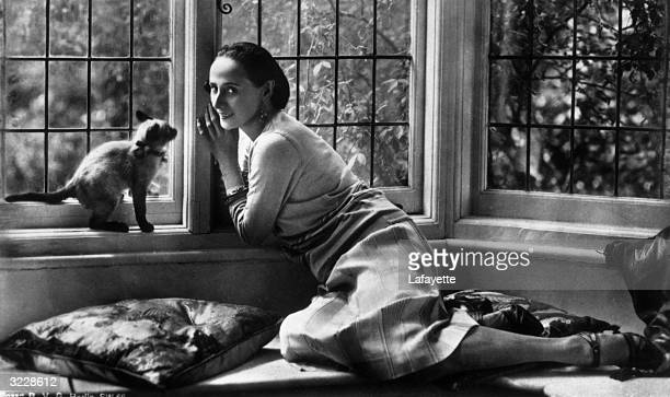 Russian ballet dancer Anna Pavlova relaxing at home with her pet cat