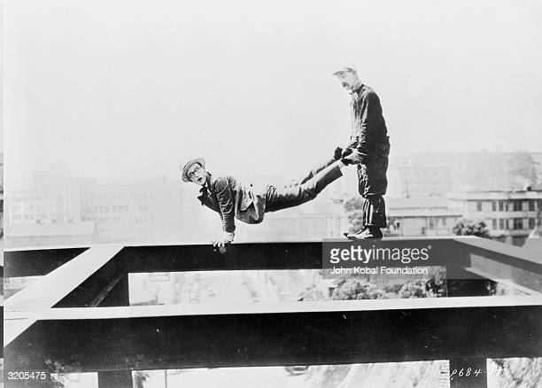 Silent comic Harold Lloyd balances on a high girder while another man holds his legs in a scene from one of his movies