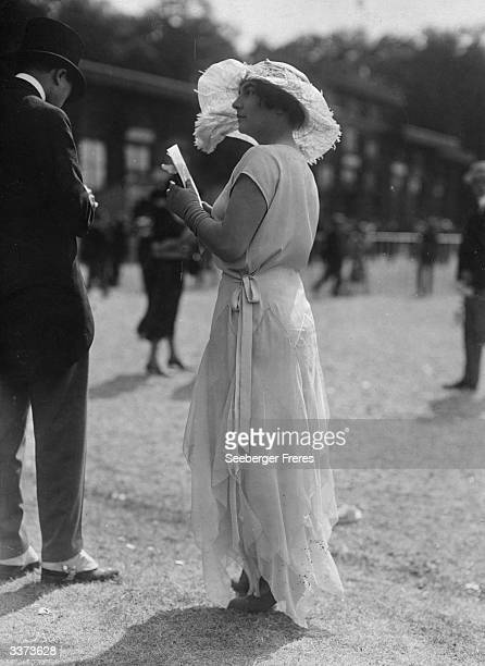 White charmeuse and georgette Grecian dress with a petal skirt worn at the races. A wide brimmed hat decorated with feathers and short gloves...