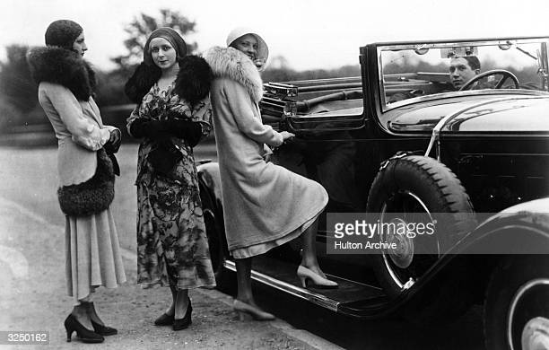 Women standing by a convertible car wearing fur lined coats