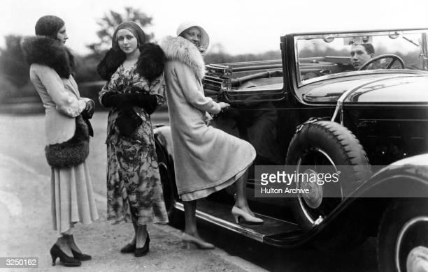 Women standing by a convertible car wearing fur lined coats