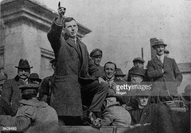 Arthur Griffith on left with hat and glasses listening to a speech Editor of 'The United Irishman' and founder of the political party Sinn Fein he...