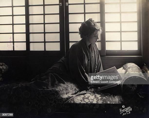 Canadian actress Mary Pickford wearing a Japanese kimono and reading a copy of 'Little Lord Fauntleroy' In 1921 she played both the title role and...