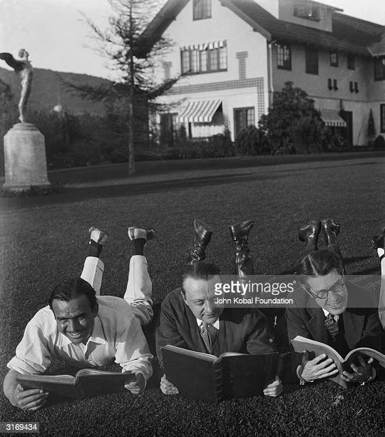 Douglas Fairbanks Snr reads the script for his swashbuckling role as D'Artagnan in Fred Niblo's the 'Three Musketeers' Next to him is scriptwriter...