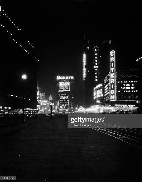 View of Times Square at night looking north on Broadway from 43rd Street Marquees for the Criterion and Loew's Theaters are illuminated Director...