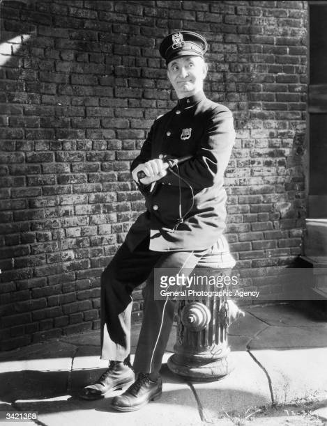 A scene from the First National film 'Bayo Nuts' with Charlie Murray as a policeman taking a rest from his beat on a fire hydrant