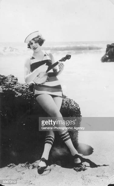 A girl in a striped swimsuit and sailor's hat playing the banjo