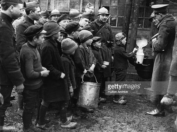 Children with buckets and containers line up to get food or drink from Belgian soldiers during the occupation of Ruhr