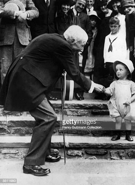 John D Rockefeller giving a nickel coin to a child in a gesture which he hoped would educate the younger generation in the ways of thrift