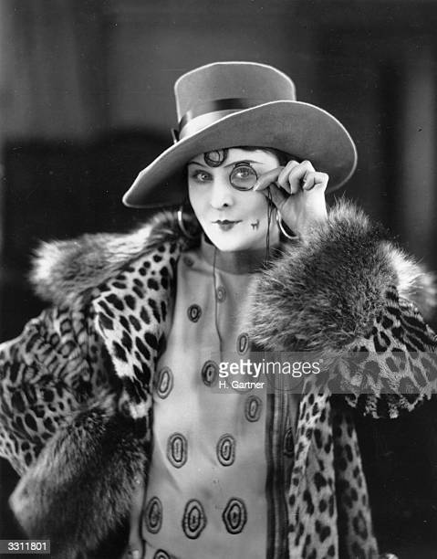 A fashion model wearing a large hat and leopardskin coat views the world through a monocle
