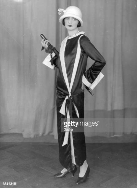 Model dressed in Norman Hartnell evening coat and cloche hat.